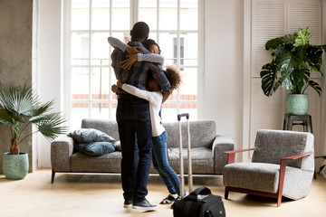 Happy African American family hug welcoming dad home