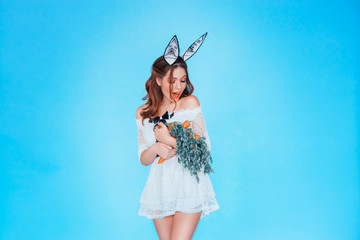 The girl in the image of a fashionable hare, enjoys an armful of carrots with green tails. Diet and healthy eating. Beautiful figure, slim body. Positive emotions, big smile on face. Blue background