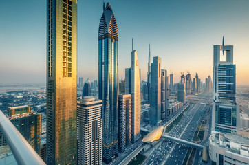 Skyscrapers and highways of a big modern city at sunset. Aerial view on downtown Dubai, United Arab Emirates.