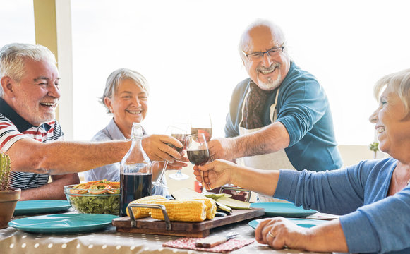 Happy senior friends toasting with red wine at barbecue dinner in terrace - Mature people dining and cheering together drinking wine on rooftop - Friendship, food and elderly lifestyle concept