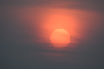 The big red sun is slowly falling, with large black clouds in front.