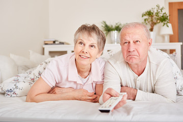 Senior citizens watch TV in bed