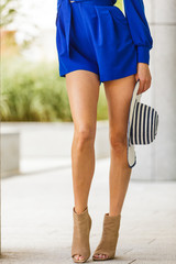 Woman wearing blue dress holding sun hat