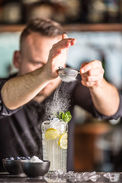 Professional barman making  alcoholic cocktail drink with fruits sugar and herbs