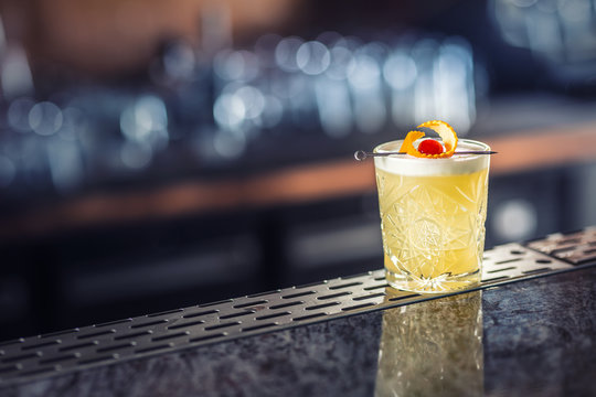 Cocktail drink whiskey sour at barcounter in night club or restaurant