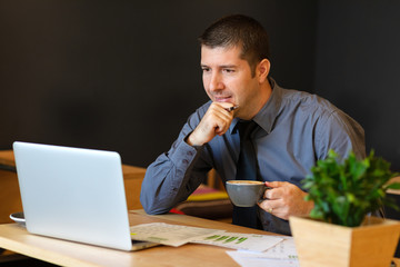 Young business man working on laptop at modern cafe analyzing financial reports