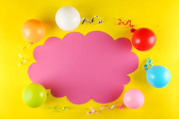 Minimal style composition with different pastel color air balloons with streamer ribbons & blank speech bubble with a lot of copy space for text on yellow background. Top view, close up, flat lay.