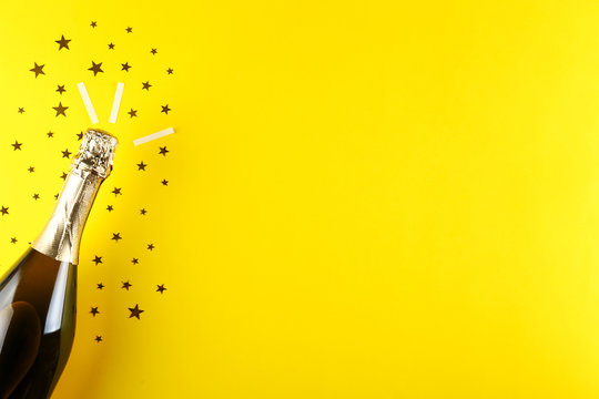 Scattered golden star shaped confetti with bottle of champagne with copy space for greeting text. Yellow background, copy space, close up, top view, flat lay.