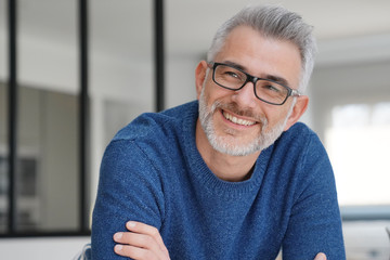 Portrait of smiling man with grey hair and glasses Wall mural