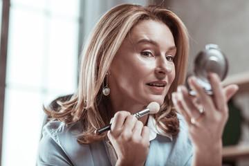 Dark-eyed woman wearing stylish earrings looking into mirror