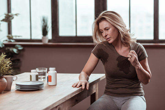 Blonde-haired stressed woman sweating and having wet t-shirt