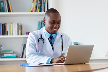 African american general practitioner working at computer