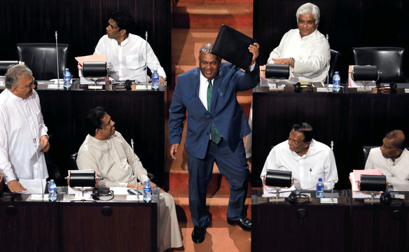 Sri Lankan Finance Minister Mangala Samaraweera shows a briefcase containg the 2019 budget proposals as he arrives at the parliament in Colombo