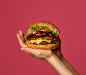 Fototapeta Woman hands hold big double cheeseburger burger sandwich with beef tomatoes and cheese obraz