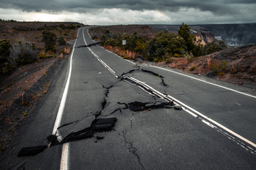 Damaged asphalt road (Crater Rim Drive) in the Hawaii Volcanoes National Park after earthquake and eruption of Kilauea (fume at upper right) volcano in May 2018. Big Island, Hawaii Wall mural