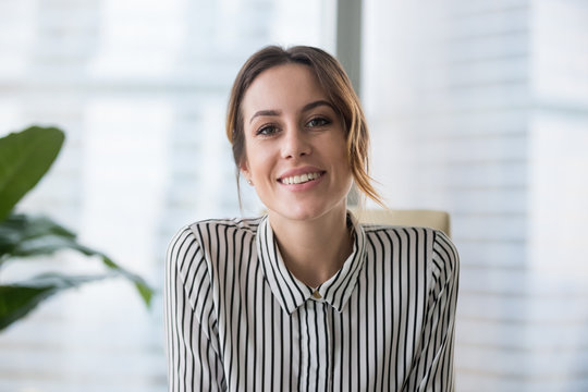 Smiling businesswoman looking at camera webcam make conference business call