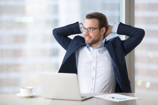Satisfied businessman taking break at workplace to relax finished work