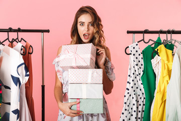 Excited woman wearing dress standing in store near clothes rack with present boxes
