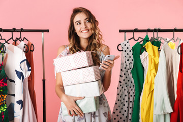Photo of pretty woman with purchase standing in store near clothes rack and using mobile phone