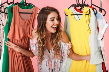 Photo of attractive woman in dress standing inside wardrobe rack full of clothes Wall mural