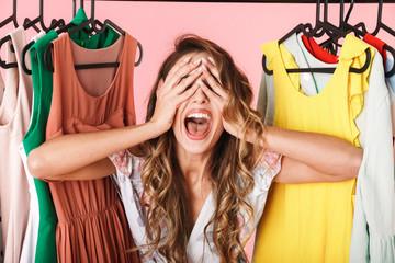 Photo of joyful woman in dress standing inside wardrobe rack full of clothes