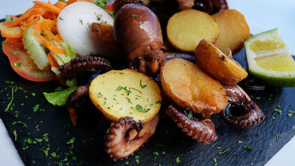 Delicious seafood meal with grilled octopus and baked potatoes and salad served on a black slate appetizer board, a typical Spanish cuisine seafood dish in El Hierro, Canary Islands, Spain