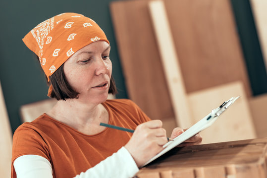 Female carpenter writing DIY project notes