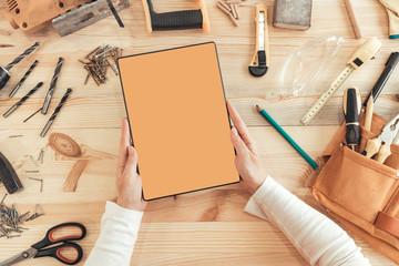 Female carpenter using digital tablet computer, mock up screen