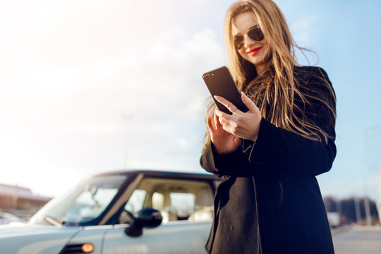 Car. Girl using smartphone.