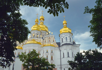 Foto op Aluminium Kiev Golden domes of Dormition church in Kyiv, surrounded by chestnut tree leaves
