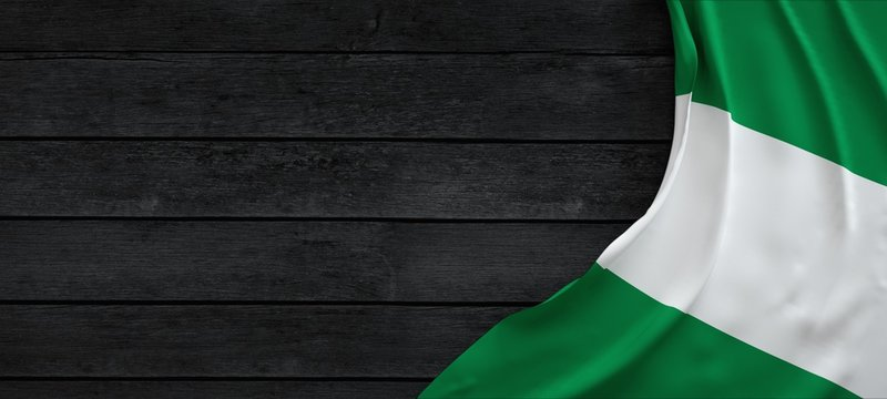 Flag of Nigeria, fabric on dark wood.