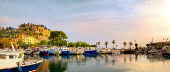 Wall Mural - Panoramic landscape with fishing boats in harbour of Cassis at sunset sunlight. France, Provence