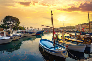 Wall Mural - Landscape with fishing boats in harbour of Cassis at sunset. France, Provence