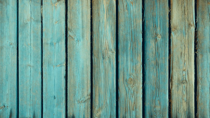 Old weathered and distressed wooden panels with traces of teal green paint, ligneous background with copy space, shabby wooden surface for natural texture backdrops
