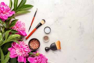 Beautiful composition of decorative cosmetics on a light background with pink peonies. Top View.