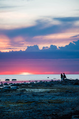 Couple at the seaside during colorful sunset.