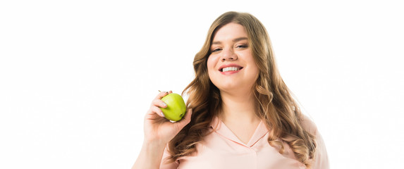 smiling plus size young woman holding ripe green apple isolated on white