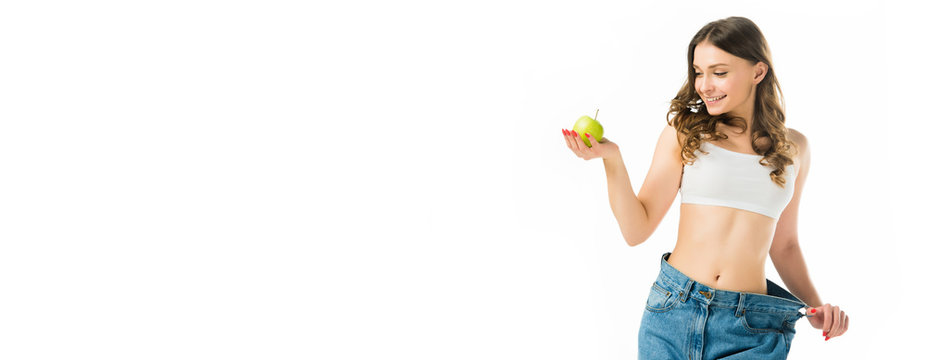 smiling slim young woman in big jeans holding ripe green apple isolated on white