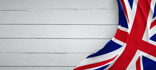 United kingdom flag, on top of white wood. Wrinkled fabric.