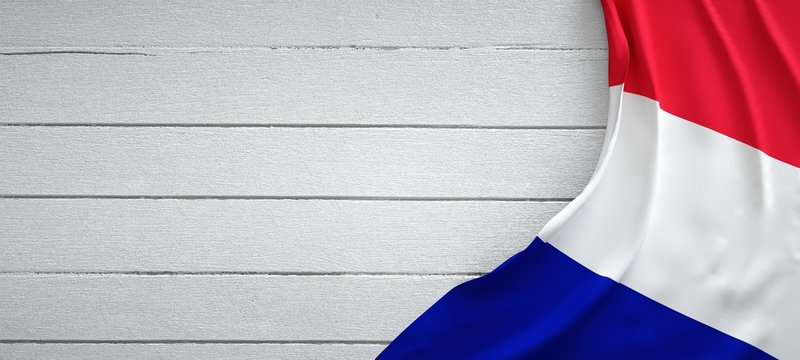 Flag of France, on top of white wood. Wrinkled fabric.