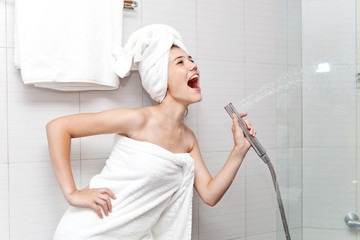 Beautiful young woman with white towel on her head sings in the bathroom