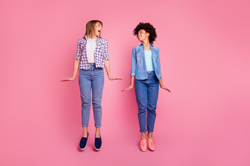 Wall Mural - Full length body size view  two funky diversity she her ladies good mood jumping high playful childish wear casual jeans denim checkered shirt clothes outfit isolated pink background