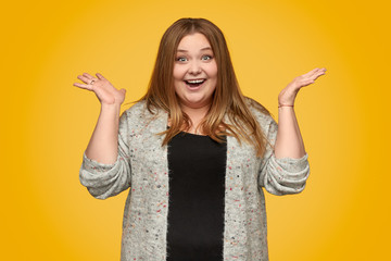 Excited plump woman gesturing with hands