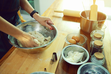 The hands of women who are kneading dough to prepare food or bread