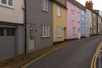 A row of colourful houses in a quiet narrow street in Lyme Regis, Dorset, England