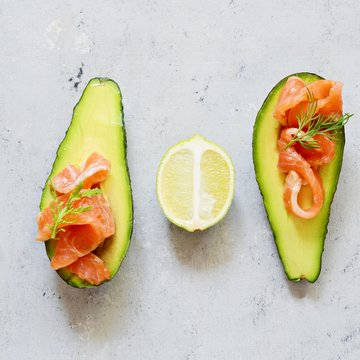 Ripe avocado boats with slices of salted trout, salmon and fresh greens on a gray background. Avocado boats stuffed with salmon with lime, spinach leaves and arugula, concept healthy food, diet.