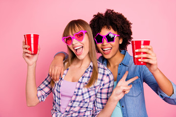 Close-up portrait of two person nice cute lovely attractive cheerful girls in casual checkered shirt showing v-sign isolated over pink pastel background