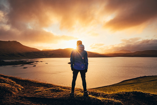 Man standing in blue jacket looking at spectacular sunset over frostadavatn lake in Landmannalaugar in Iceland