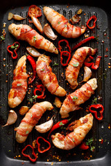 Spicy chicken meat, Grilled chicken tenderloin wrapped with bacon with addition chili peppers, garlic and herbs on grill plate, close-up, top view