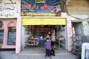 Marwa Khalid, 28, poses for picture with her children at her temporary shop in the old city of Mosul